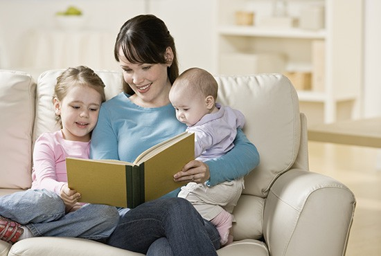 Mother reading to her children in their comfortable home.