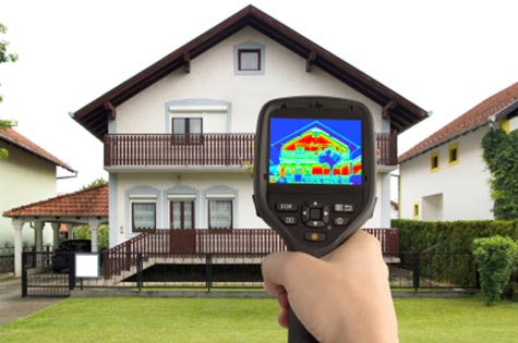 A person performing a thermal scan on a home